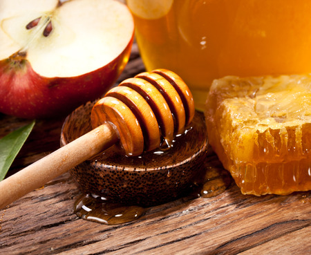honey apple: Honeycombs and wooden dripper. Can and apple on the background.