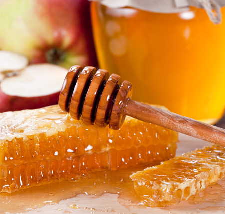 honey apple: Honeycombs and wooden dripper. Honey can and apple on the background.