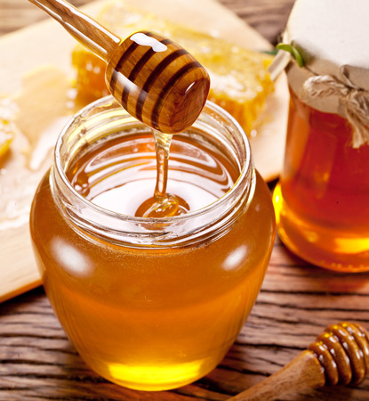 golden honey: Honey flowing into glass can from wooden stick.