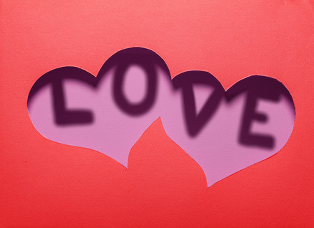 Two hearts cutout in red paper with word LOVE inside.Card design. photo