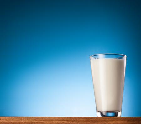 Verre de lait sur un fond bleu. Banque d'images - 35572912