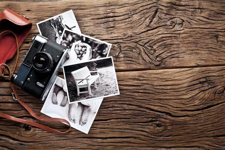 Alte Messsucherkamera und Schwarz-Weiß-Fotos auf dem alten Holztisch.