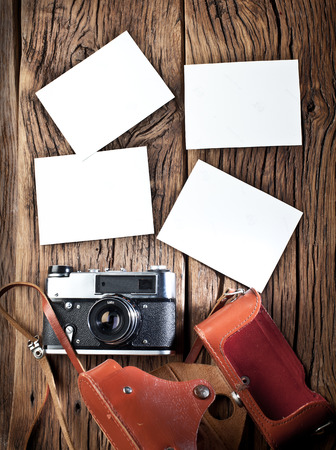 rangefinder: Old rangefinder camera and black-and-white photos on the old wooden table. You can inset your images here.