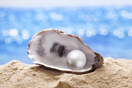 Shell con una perla en una arena de mar.