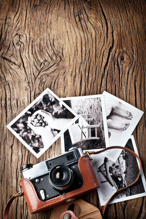 rangefinder: Old rangefinder camera and black-and-white photos on the old wooden table.