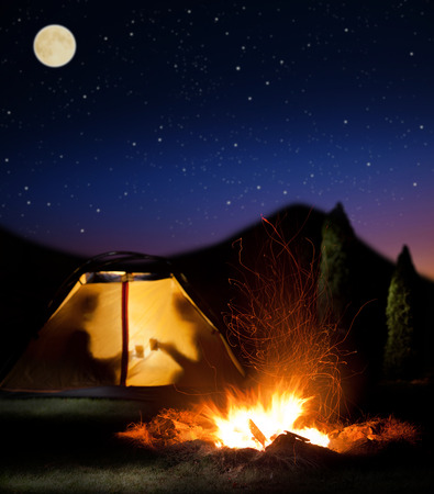 Camp shines at night. The campfire in the front as the symbol of adventure and romantic. Stock Photo