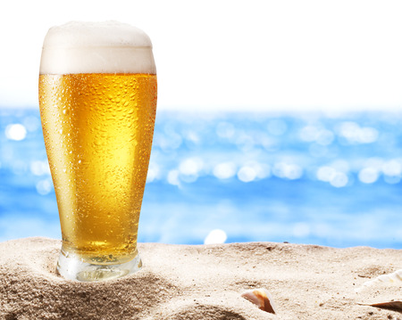glasses of beer: Photo of cold beer botle in the sand. Sparkling sea at the background. Stock Photo