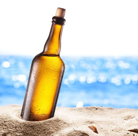 Foto van koud bier botle in het zand. Glinsterende zee op de achtergrond.