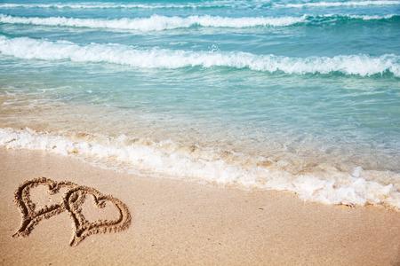 Hearts drawn on the beach sand. photo