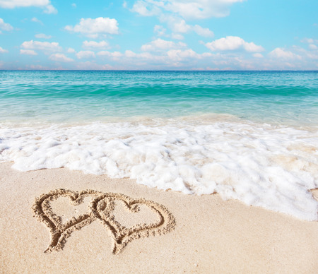 sand drawing: Hearts drawn on the beach sand.