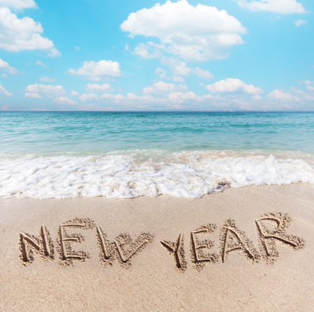 New Year words written on the beach sand. photo