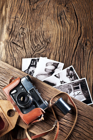 blackandwhite: Old rangefinder camera and black-and-white photos on the old wooden table.