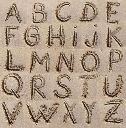 handwrite: Alphabet (ABC) written on sand.