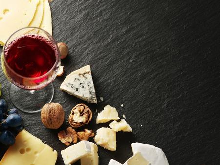queso: Los diferentes tipos de quesos con copa de vino y frutas. Vista superior. Foto de archivo