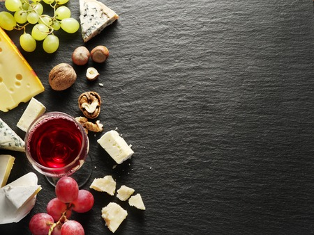cheese slices: Different types of cheeses with wine glass and fruits. Top view.