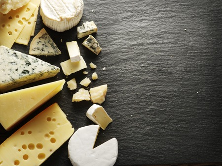calorie: Different types of cheeses on black board.