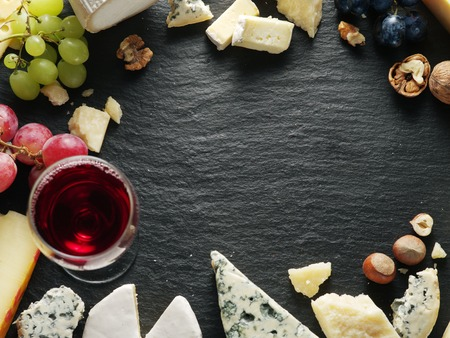 trays: Different types of cheeses with wine glass and fruits. Top view.