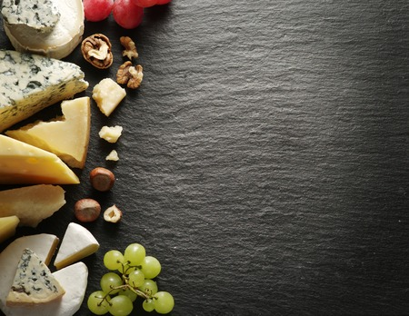 Different types of cheeses with wine glass and fruits. Top view.