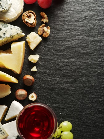 grape: Different types of cheeses with wine glass and fruits. Top view.