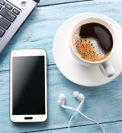 modern lifestyle: Coffee break. Office table with different gadgets on it. Top view. Stock Photo