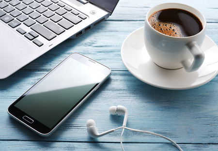 Coffee break. Office table with different gadgets on it. Top view. Stock Photo