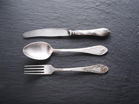 Silberbesteck auf einem dunkelgrauen Hintergrund. Standard-Bild - 36826264