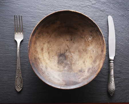 silver cutlery: Silver cutlery and old wooden plate on a grey background. Stock Photo