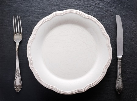 silver cutlery: Silver cutlery and vintage plate on a dark grey background.