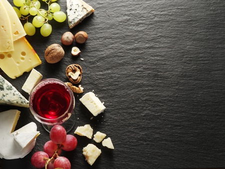 farm background: Different types of cheeses with wine glass and fruits. Top view.