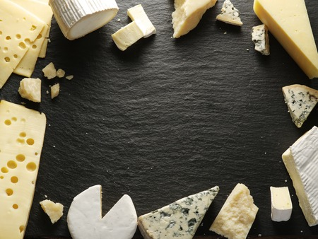 Different types of cheeses arranged as a frame on black board.