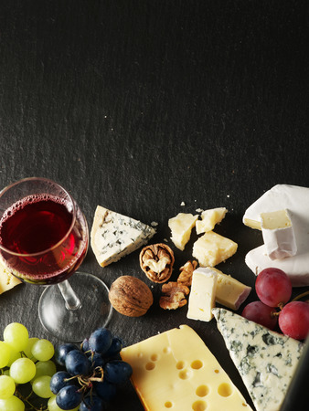 grape fruit: Different types of cheeses with wine glass and fruits. Top view.