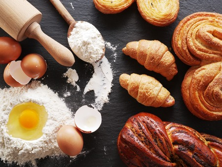 bakery products: Dough preparation. Baking ingredients: egg and flour on black board. Stock Photo