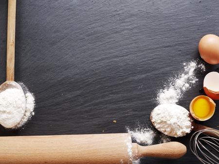 Teigzubereitung. Backzutaten: Ei und Mehl auf Tafel. Standard-Bild - 36833465