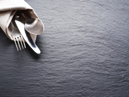 black and silver: Silver cutlery on a dark grey background.