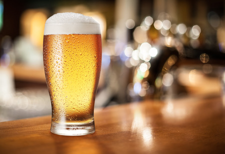 vidrio: Vidrio de cerveza en la barra del bar.