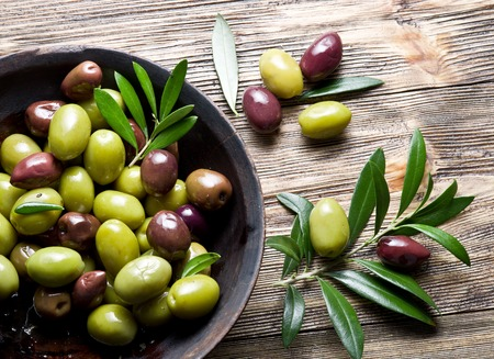 olive green: Wooden bowl full of olives and olive twigs besides it.