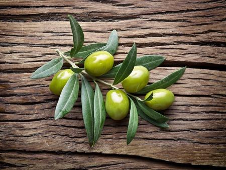 Ramita de olivo en mesa de madera vieja.