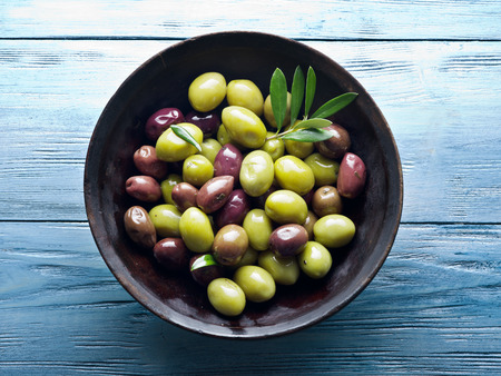 olive: Wooden bowl full of olives and olive twigs besides it.
