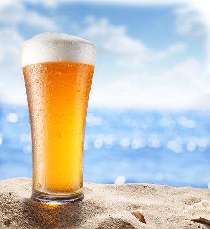 砂の中の氷のビール グラス。背景にぼやけている海。