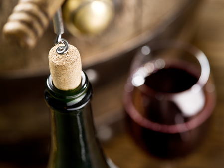 wine cellar: Opening of a wine bottle with corkscrew with wooden barrel on the background.