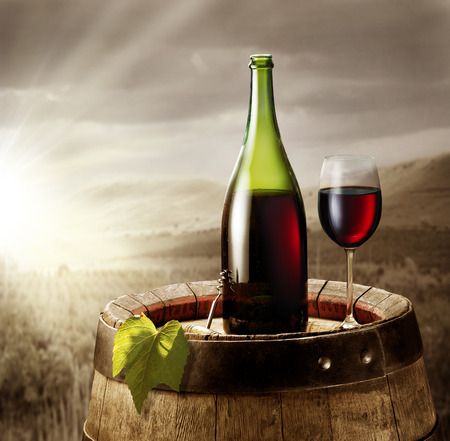 vineyard at sunset: Still-life with glass of wine and bottle on the barrel in the vineyard.