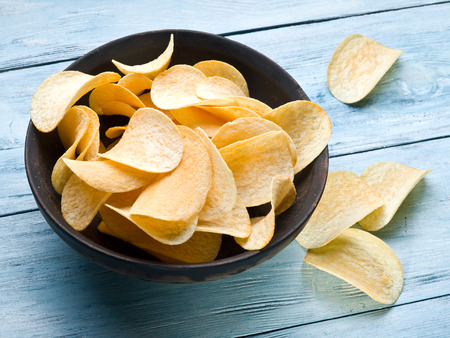 Potato chips on a blue wooden .