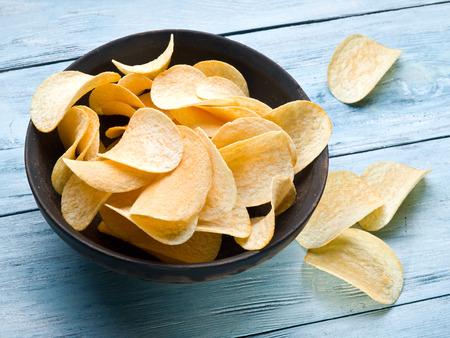prepared potato: Potato chips on a blue wooden .