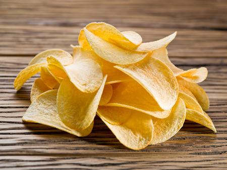Potato chips on a wooden background. Фото со стока