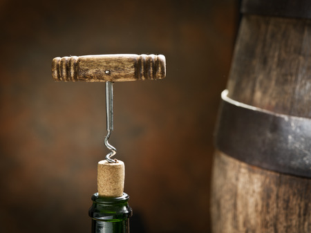 wine testing: Opening of a wine bottle with corkscrew with wooden barrel on the background.