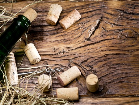 Wine bottle and corks on an old wooden table. photo