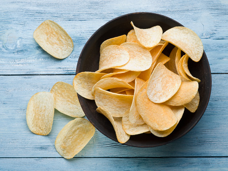 in the chips: Potato chips on a blue wooden background.