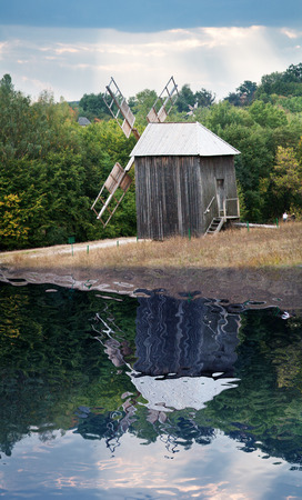 near side: Old wooden mill near the pond somewhere in the country side. Stock Photo