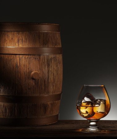 matured: Glass of matured whiskey with ice cubes in it and old wooden barrel.