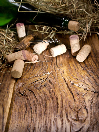 wine testing: Wine bottle and corks on an old wooden table.